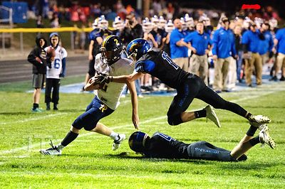 Wilton's Cory Anderson (11) forces  Iowa City Regina's Michael Conlon (2) out of bounds on a quarterback run play during the ...