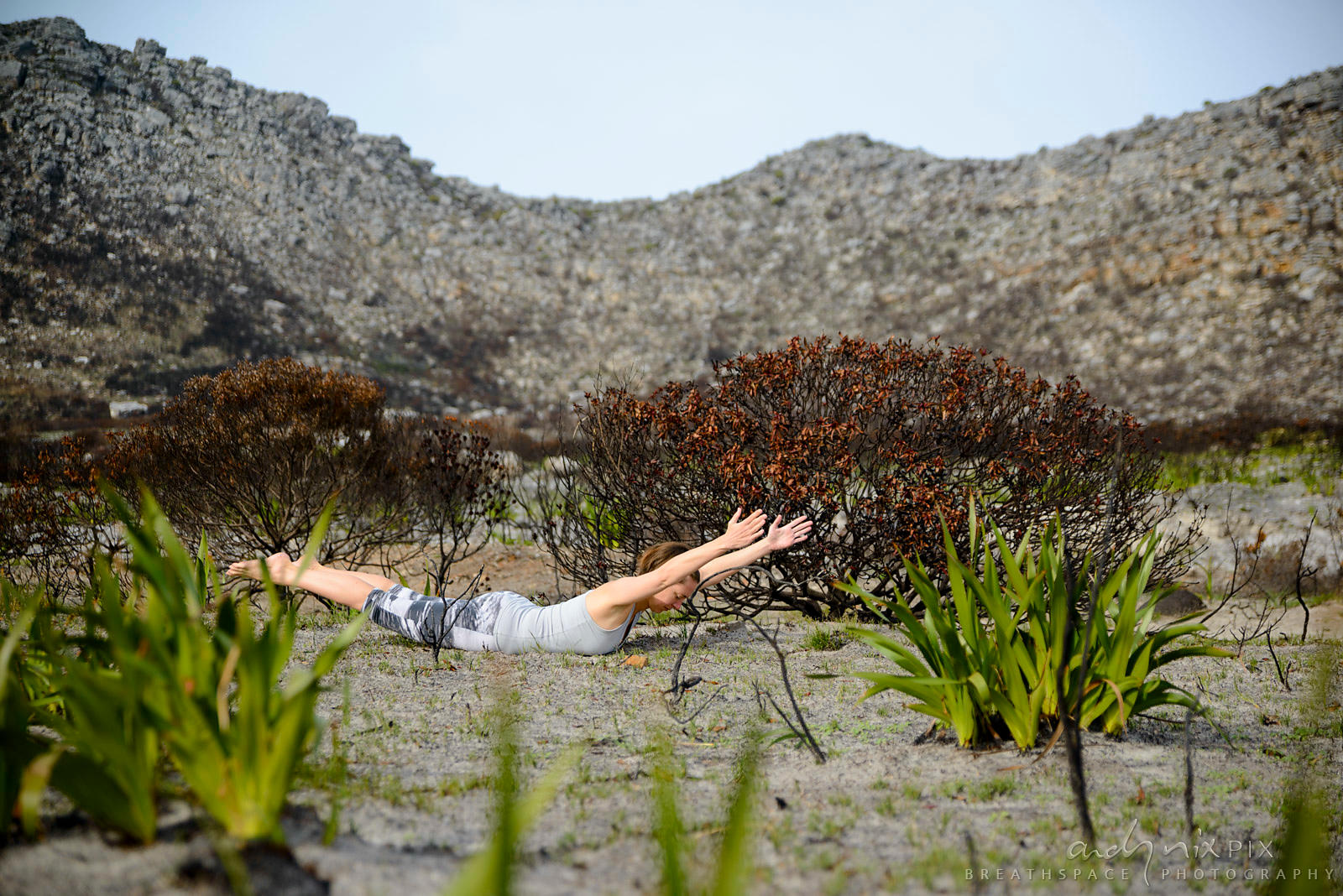 Woman doing yoga in fynbos regenerating after fire
