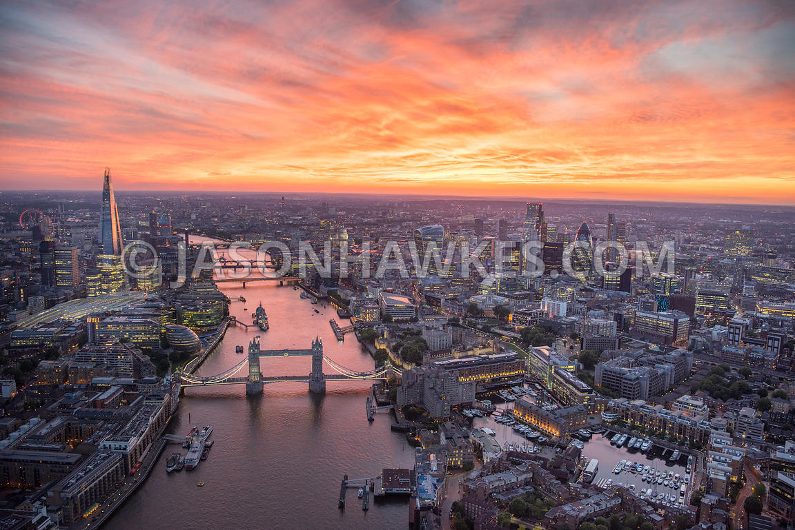 Dusk aerial view over Tower Bridge, City of London, Shad Thames, St Katherine's Dock, Tower of London, London.