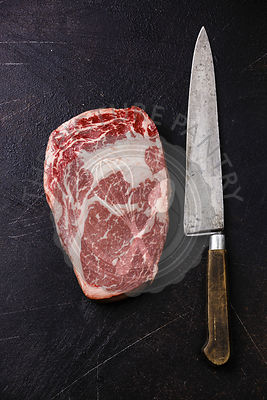 Raw fresh marbled meat Steak Rib eye Black Angus and kitchen knife on dark background