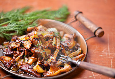 Fried chanterelles with potatoes and onion in batch pan on the table