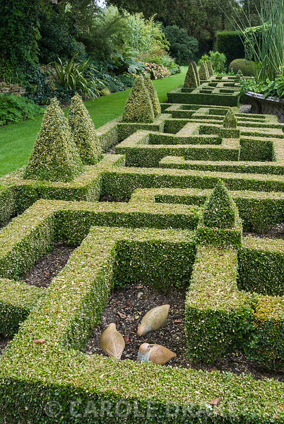 Bird sculptures nestle inside the box knot garden. Bourton House, Bourton-on-the-Hill, Moreton-in-Marsh, Glos, UK