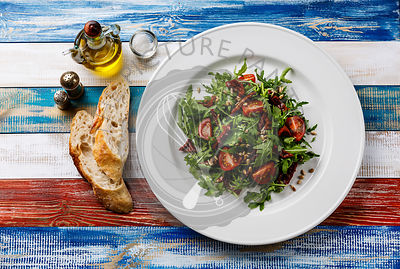 Salad with arugula, sun-dried tomatoes and sunflower seeds on white plate on wooden background