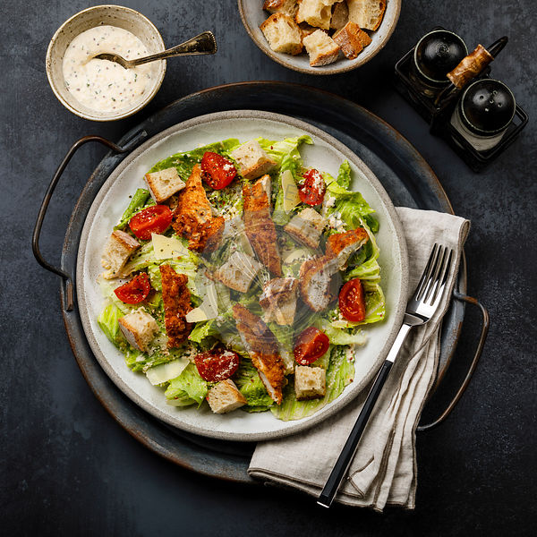 Caesar salad with Chicken breast meat on metal tray on dark background