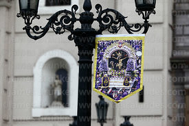 Señor de los Milagros / Lord of Miracles banner hanging from ornate street lamp and cathedral facade, Plaza de Armas, Lima, Peru