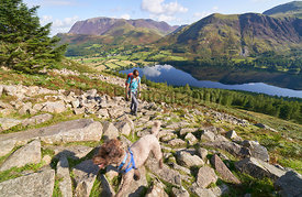 A hiker and dog on route to the summit of Red Pike with views of Lake Buttermere, Robinson, Whiteless Pike, Wandope and Grasmoor in the distance. The English Lake District, UK.