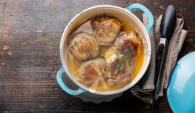 Roast chicken stew in cast iron pan on wooden background copy space