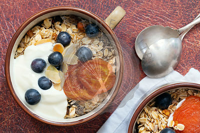 Close-up view of muesli in a bowl topped with dried apricots, blueberries and yoghurt.