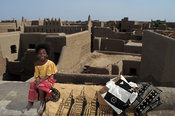 Girl sitting on a traditional flat mud rooftop selling traditional mud-cloth paintings or bogolan, Djenné, Mali
