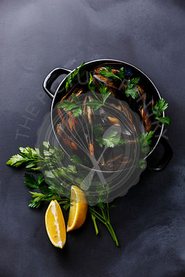 Mussels Clams in cooking pan with parsley and lemon on dark background