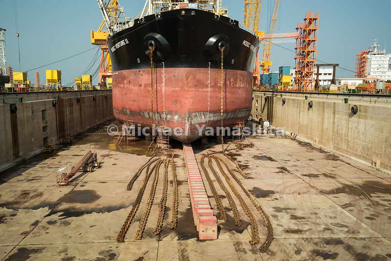 A vessel sits atop keel blocks in a dry dock while undergoing repairs at Semcorp Marine Tuas Boulevard Yard.