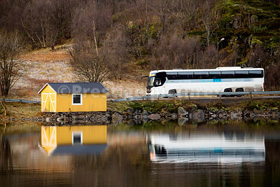 Yellow boathouse and white coach reflected in the fjord waters