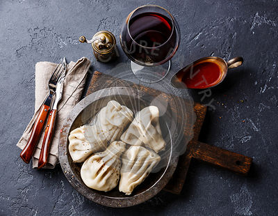 Georgian dumplings Khinkali with meat, tomato spicy sauce satsebeli and wine on dark stone background