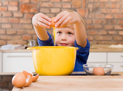 boy adding eggs to bowl