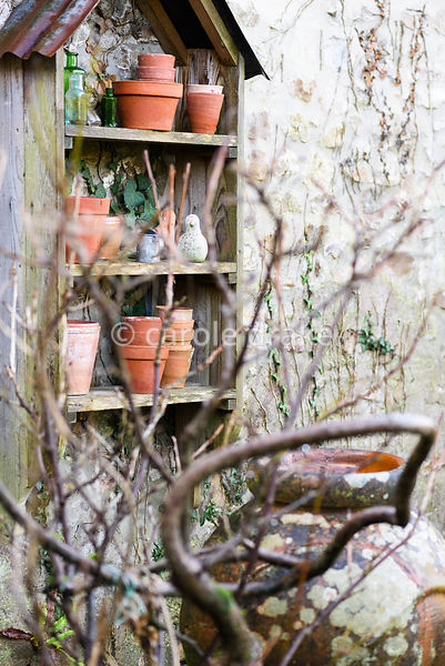 Outdoor display shelves with terracotta pots, glass bottles and birds