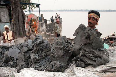 A man extracts clay from the Hooghly River in Kolkata India. It will be sold to sculptors in nearby Kumartoli (Potter's Town)...