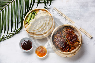 Sliced Peking Duck in bamboo steamer served with fresh cucumber, roasted wheaten chinese pancakes and sauce Hoysin on white w...