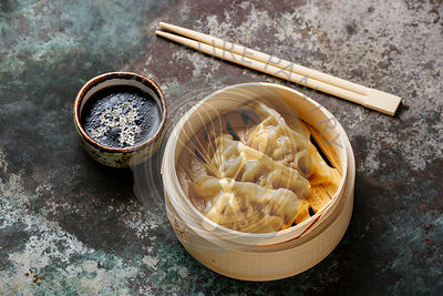 Steamed dumplings Gyoza in bamboo steamer with chopsticks and sauce on metal background