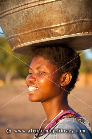 Woman carrying a bucket on her head, Cape Maclear, Malawi