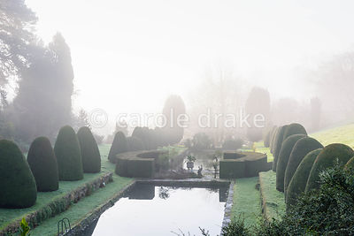 View over the Canal Garden on a winter's morning at Mapperton, Dorset where swimming pool and lily pond are framed by clipped...