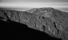 Black and white image of a rocky ridge with views of a wind farm out at sea In the English Lake District, UK.