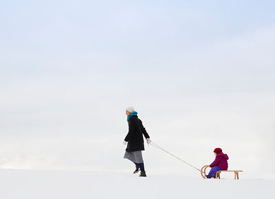 Mother pulling daughter on sled in snow