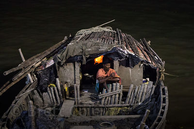 A boatman on his boat at night, Hooghly River, Kolkata, India.