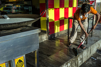 A Sweetshop Owner Cleans The Steps In Front Of His Shop