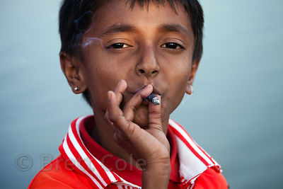 Children in the town of Chingrihata smoke cigarettes on a small footpath in the East Kolkata Wetlands, Kolkata, India. Small ...