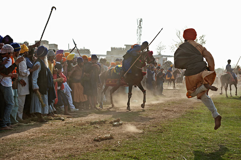 A man leaps to safety from the speeding horse
