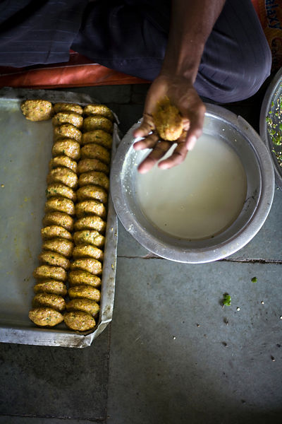 India - Delhi - A boy moulding vegetable patties to fry Babu Shahi Bawarchi