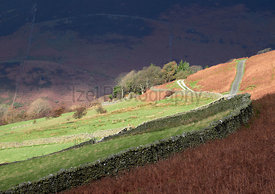 Farmland below the mountain summits on a sunny day in the English Lake District, UK.