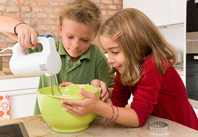girl and boy stirring dough