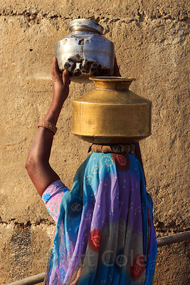 A lady with metal water pots on her head in Kishanpura Goyla village, Rajasthan, India