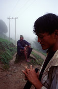 Two peasants pause to rest on a hillside, Dolakha region, Nepal