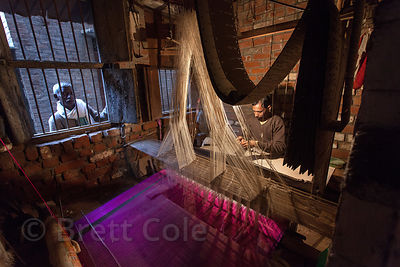 A silk weaver works at a small anonymous workshop in Varanasi, India. Varanasi is famous for its fine silk.