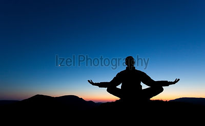 A man is meditating, in pray on the summit of a mountain as the sun sets.