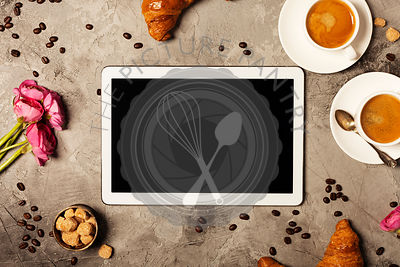 Tablet, coffee and croissants on grey stone background. Top view. Flat lay style.