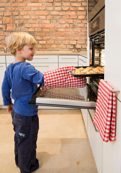 boy taking baked cookies from oven