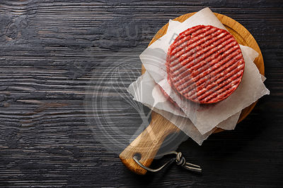 Raw Ground beef meat Burger steak cutlets on black burned wooden background copy space