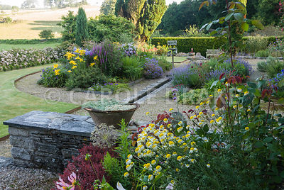 Parterre garden beside the house is split onto two levels with beds including a mix of yellow and blue perennials, shrubs and...