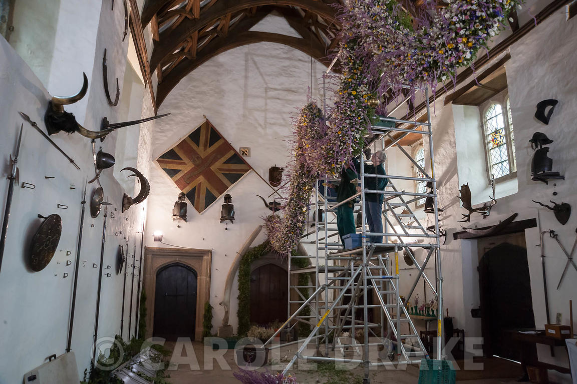 Volunteers on a scaffolding tower constructing the Christmas garland in the Great Hall. Cotehele, St Dominick, nr Saltash, Co...