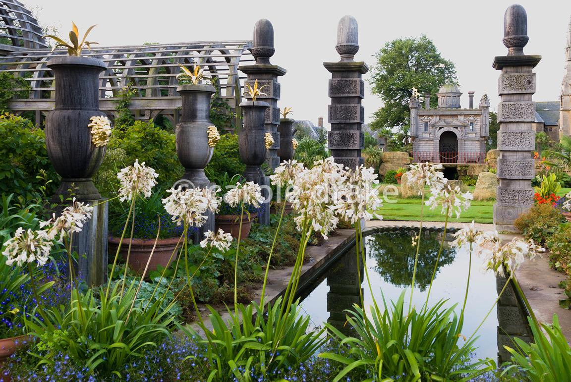 Rill pool flanked by turned oak urns spouting water, with gilded agaves in their tops. Planting includes Alchemilla mollis an...