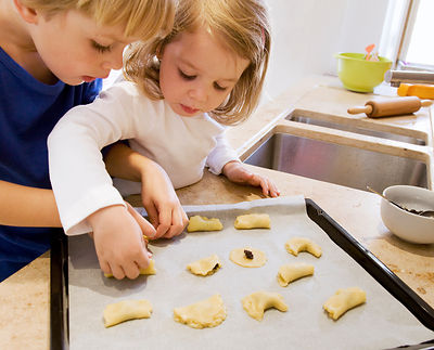 girl, boy preparing cookies for baking