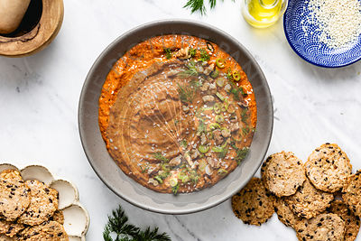 Muhammara served in a bowl on a marble surface
