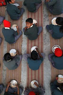 Top-down view of students eating lunch at a school in Varanasi, India operated by Dutch NGO Duniya (duniya.org).