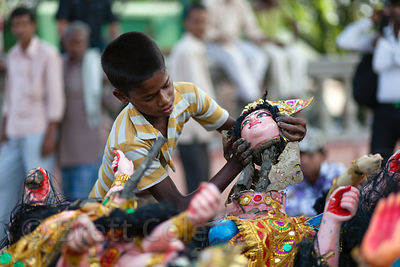 A boy takes the heads off of religious idols at Babughat in Kolkata, India, during the Durga Puja festival. The idols are imm...