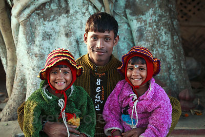 Portrait of a father and his daughters in the rural farming area of Dhapa, Kolkata, India.