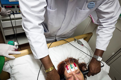 This patient is areceiving electro-shock therapy to treat her severe depressive phases. Nowadays, patients are anesthetized to undergo the treatment, monitored by a full team of healthcare workers, and kept under strict control to avoid pain or unwanted side-effects. Nyon, Switzerland, 26 January 2018...Taken as I was embedded in the team. Photographer did not influence the scene in any way (treatment routine is well oiled), nor gave directions to anyone.