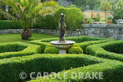 Formal box parterre with central water feature surrounded by box spheres, date palms and lavender in pots on wall above. Edno...